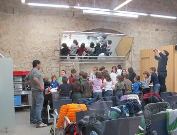 Uns escolars fan un taller a l'obrador de l'MX. / © Gg